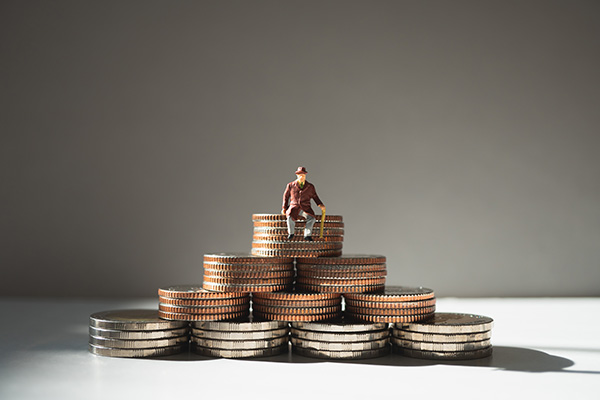 Miniature people, old man sitting on stack coins using as job re